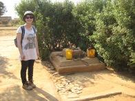 Anna beside a standard well