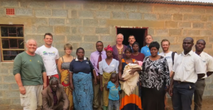 Bettina (in red scarf) outside her new house